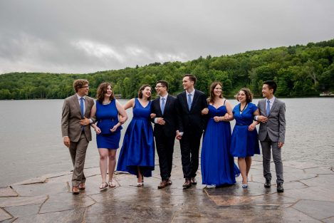 two grooms and their wedding party laughing and walking by the lake.