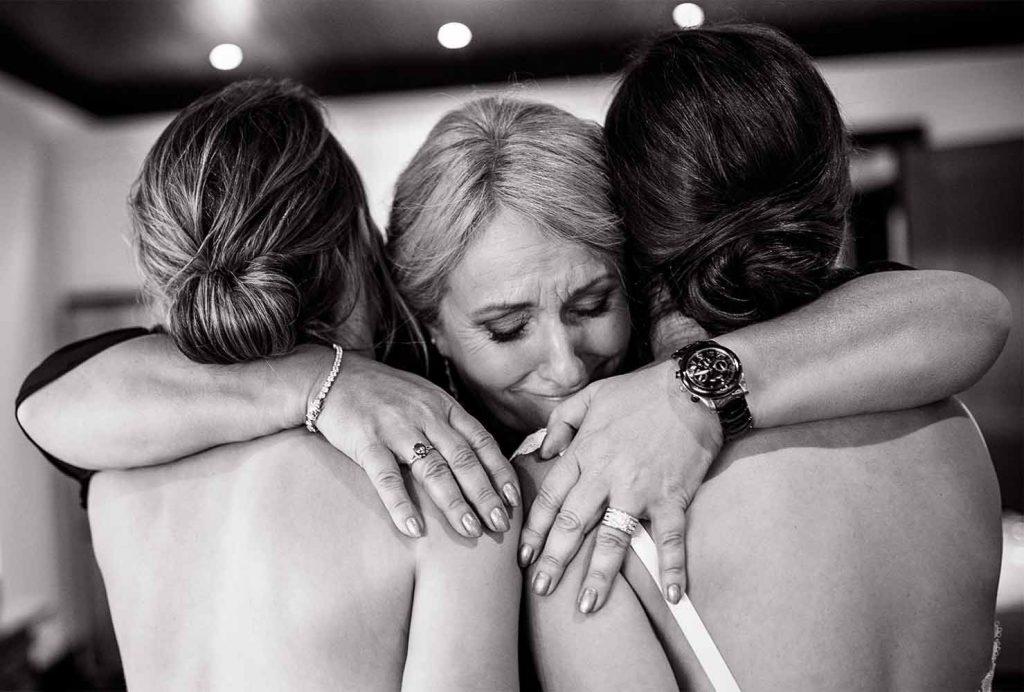 Mom hugs her daughters at Muskoka wedding